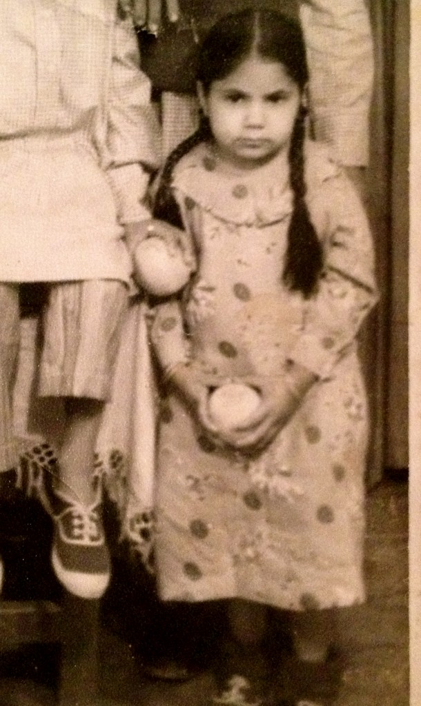 Year: 1975. Puran Kaur (about age 7) daughter of Rattan Kaur (above) posing with an orange. Punjab. Source: Private Collection