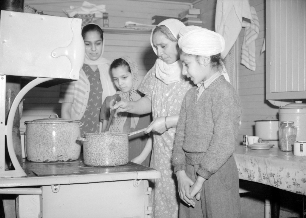 Jan 1943. Sikh family standing around a stove. Photographer: Jack Lindsay of the Vancouver News-Herald. Source: City of Vancouver Archives.