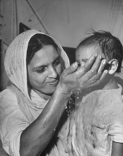 1946. Harmindar Sahib. A Sikh mother holds her child who is drinking water from her hand after she has bathed her feet & his in the stone bath at the entrance of Harmindar Sahib (Golden Temple). Photo by Margaret Bourke-White. The LIFE Picture Collection. Getty Images.