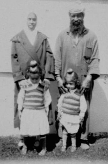 1931. Harnam Kaur Koka (left) and Ran Singh Koka (right) with their two daughters Karm Kaur (3 years old at left) and Tej Kaur (two years old). They are standing in front of the Chillwack General Hospital, British Columbia. Karm Kaur went on to marry into a Rai family and Tej Kaur married into a Gill family. Ran Singh Koka worked on his family farm in India but fled a plague that killed a number of his family members before coming to BC in 1905. He arrived as a stowaway in Vancouver with two other men from his village aboard a Japanese cargo ship. At the harbour he was confronted by police and dogs but managed to escape. He found work with the CPR and BC hop companies in Agassiz. He travelled back to India in 1922 and returned with his wife, Harnam Kaur in 1925. They later started a dairy farm and also grew corn, hay, alfalfa, clover and wheat. Source: thereach.ca