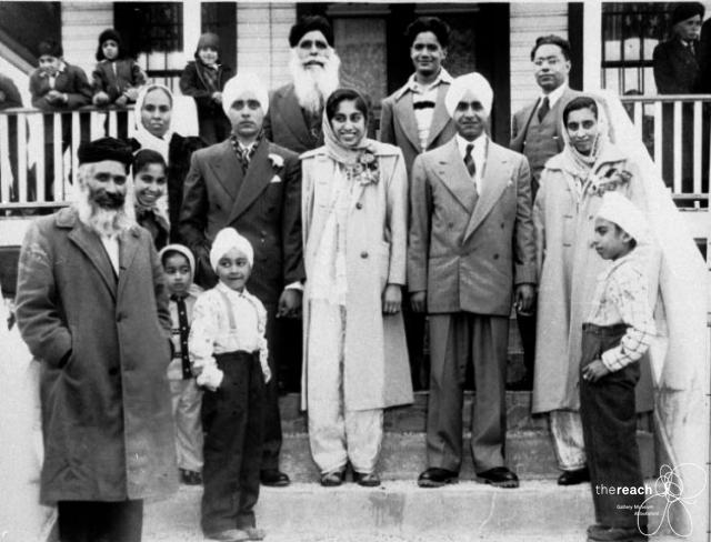 "1949. Abbotsford Gudwara. Koka, Rai, and Gill familes after the double wedding of sistesr Karm Kaur Koka and Tej ""Lucky"" Koka. R to L: Ran Singh Koka, father of the brides, Gladys Koka, brides' younger sister, Harnam Kaur koka, brides' mother, Beverley Koka, brides' youngest sister, Bobby Koka, brides' youngest brother, Gian Rai, groom, Mangle Singh Gill, father of one of the grooms, Karm (Koka) Rai, bride, John Koka, brides' oldest brother, Sewa Gill, groom, Atma Singh Rai, father of the groom, Tej ""Lucky"" Kok Gill, bride, George Koka, bride's brother. Source: TheReach.ca"