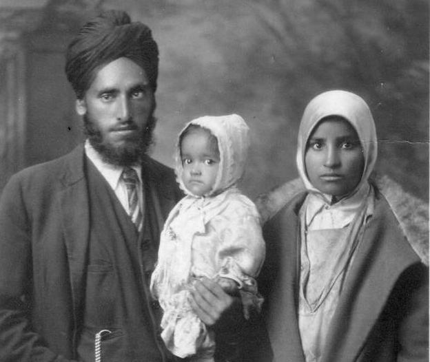 1929, Nand Singh Banga holds his oldest child, Bhagwan Kaur with his wife, Dhan Kaur. This photo was taken when the family lived in New Westminster, British Columbia, Canada. Nand worked in Queensborough at the Mohawk Lumber Company. The family moved to Abbotsford in 1951 when Nand and his sons returned from India. Dhan Kaur and Bhagwan stayed in India and did not return. Source: Thereach.ca