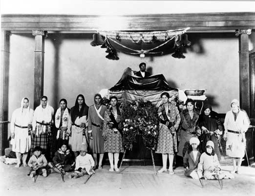 1927. Women of the community with the Guru Granth Sahib in the Stockton Gurdwara, California. Front row, left to right: Hari and Blanche Dhillon, next three children unidentified; middle row, left to right: Mrs. Pooni, Rattan Kaur, next three women unidentified, Karm and Kartar Dhillon (wearing identical dresses), next three women unidentified; back: Granthi Bhola Singh. Coutesy of Sohan Singh Pooni, Surrey, British Columbia. Source: http://www.lib.berkeley.edu/SSEAL/echoes/chapter8/chapter8_5.html