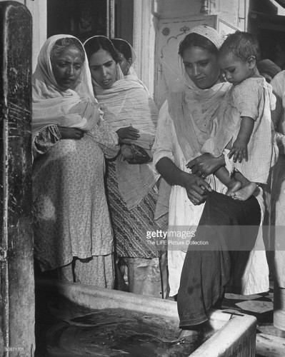 Sikh mother holding child as she washes her feet before entering the Golden Temple for services as other women wait their turn. September 01, 1946. Credit: Margaret Bourke-White. Source: http://www.gettyimages.com/detail/news-photo/sikh-mother-holding-child-as-she-washes-her-feet-before-news-photo/50871701