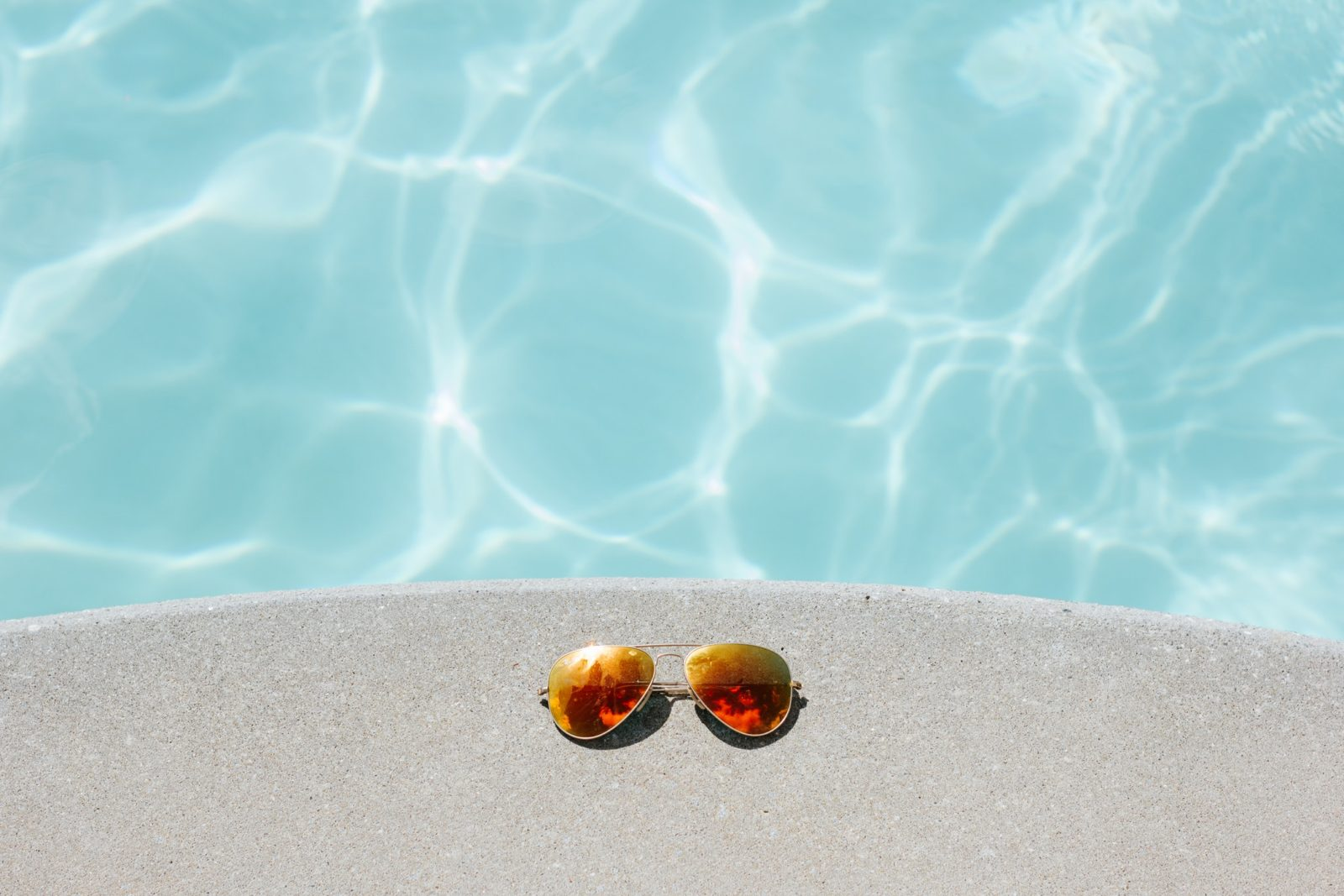 Sun glasses next to swimming pool